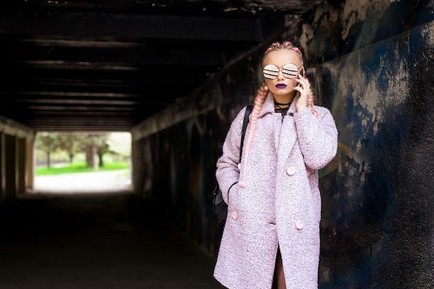 Modna kobieta z różowymi warkoczami w różowym płaszczu z jasnym makijażem i okrągłymi okularami pozuje na ulicy w tunelu.