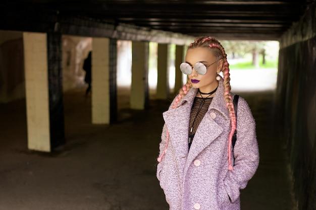Modna kobieta z różowymi warkoczami w różowym płaszczu z jasnym makijażem i okrągłymi okularami pozuje na ulicy w tunelu