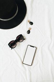Modna kompozycja makiet z eleganckimi dodatkami damskimi na białej pościeli. kapelusz, okulary przeciwsłoneczne, kolczyki, smartfon z ekranem do kopiowania