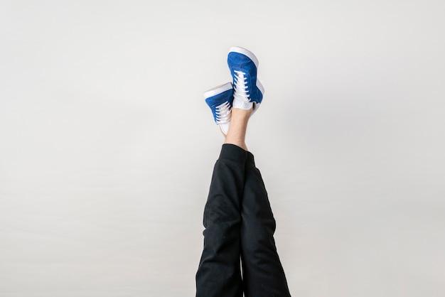 Modna koncepcja modna, proste nogi w tenisówkach w powietrzu przy ścianie, do góry nogami