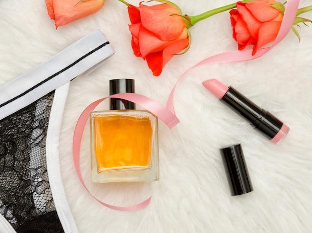 Modna koncepcja. perfumy, szminki, koronkowa bielizna i róże na białym tle.