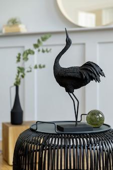 Modna koncepcja wnętrza salonu z czarnym rattanowym stolikiem kawowym, okrągłym lustrem, kwiatami w wazonie, latarnią, półką, drewnianą kostką i eleganckimi akcesoriami osobistymi w nowoczesnym wystroju domu.