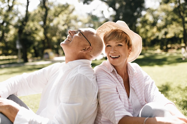 Modna krótkowłosa dama w lekkim kapeluszu i bluzce w paski, uśmiechnięta i siedząca na trawie ze starym mężczyzną w okularach i białej koszuli na zewnątrz.