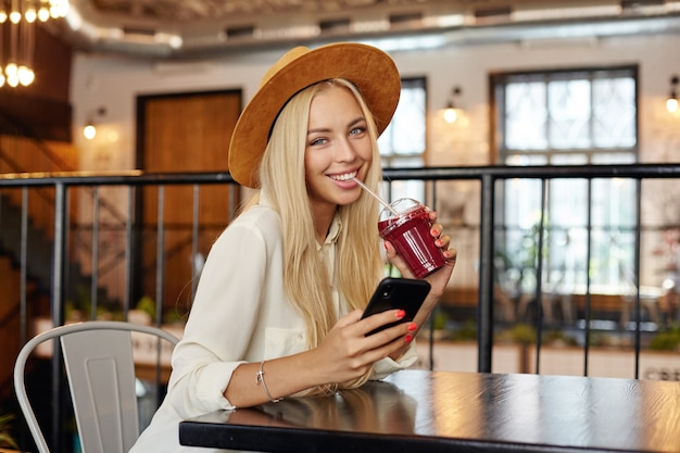 Modna, ładna młoda, długowłosa blondynka o pięknych niebieskich oczach, patrząca z uroczym uśmiechem, pijąca smoothie ze słomką, siedząc nad wnętrzem restauracji