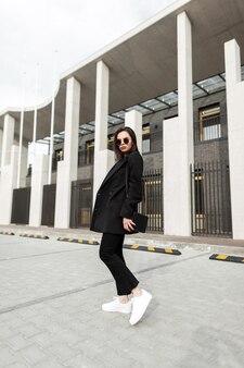 Modna ładna młoda kobieta w stylowej czarnej marynarce z torebką vintage spacery w pobliżu nowoczesnego budynku w mieście. piękny miejski model dziewczyna podróżuje na ulicy. codzienne modne ubrania młodzieżowe dla kobiet.