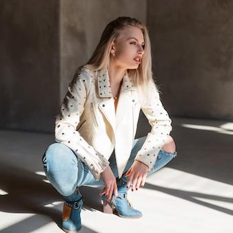 Modna ładna młoda seksowna kobieta w stylowej skórzanej kurtce z metalowymi nitami w podartych dżinsach w kowbojskich butach siedzi w słoneczny wiosenny dzień w pomieszczeniu