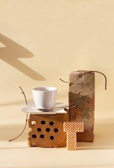 Modna martwa natura ze starymi cegłami, suszonymi roślinami, filiżanką kawy i ciasteczkami. wcześniej używane przedmioty w nowoczesnej przestrzeni życiowej.