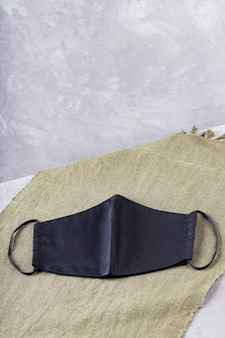 Modna maska ochronna na zielonym materiale. czarna maska na ostatecznym szarym tle. skopiuj miejsce