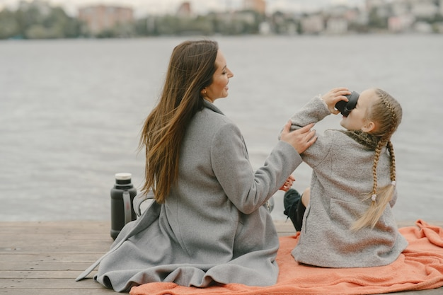 Modna matka z córką. ludzie na pikniku. kobieta w szarym płaszczu. rodzina nad wodą.