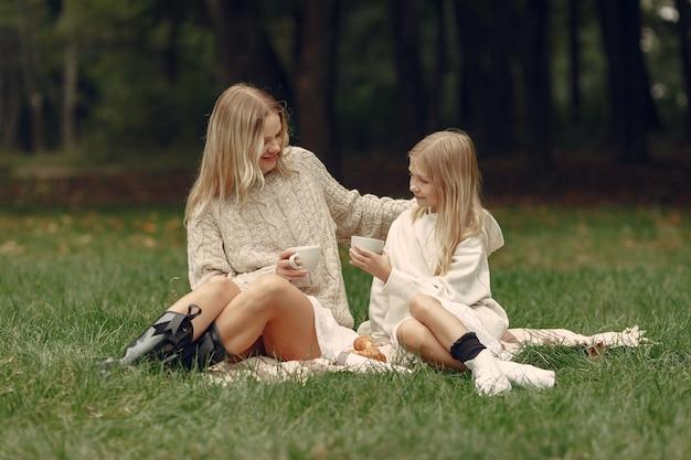 Modna matka z córką. ludzie siedzący na trawie