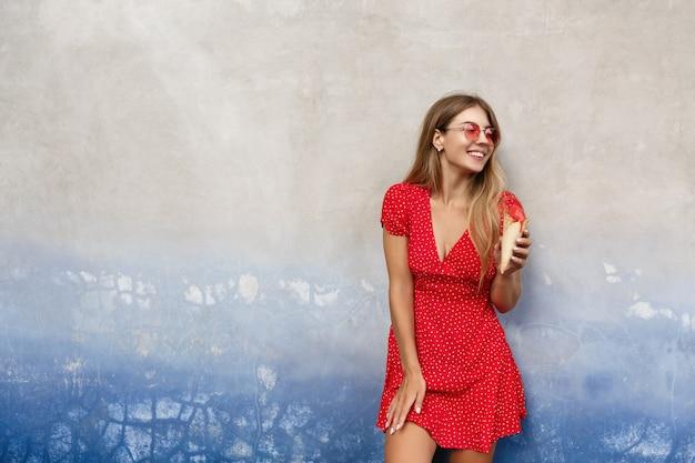 Modna miejska dziewczyna w czerwonych okularach przeciwsłonecznych i letniej sukience, je lody na świeżym powietrzu, opierając się o betonową ścianę i odwracając wzrok