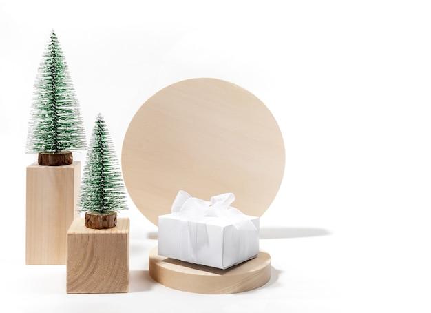 Modna minimalna świąteczna kompozycja z ozdobną choinką i pudełkiem prezentowym diy na drewnianych podium na białym tle. świąteczna karta z pozdrowieniami kreatywnych. makieta. skopiuj miejsce.