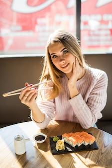 Modna młoda blondynka w białym swetrze je sushi na obiad przy małej kawiarni