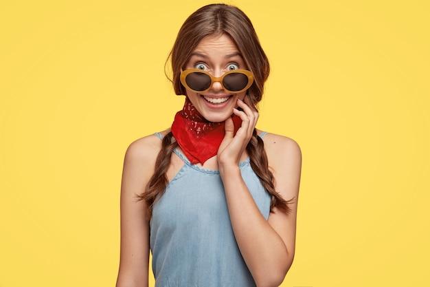 Modna młoda brunetka pozuje przeciw żółtej ścianie z okularami przeciwsłonecznymi