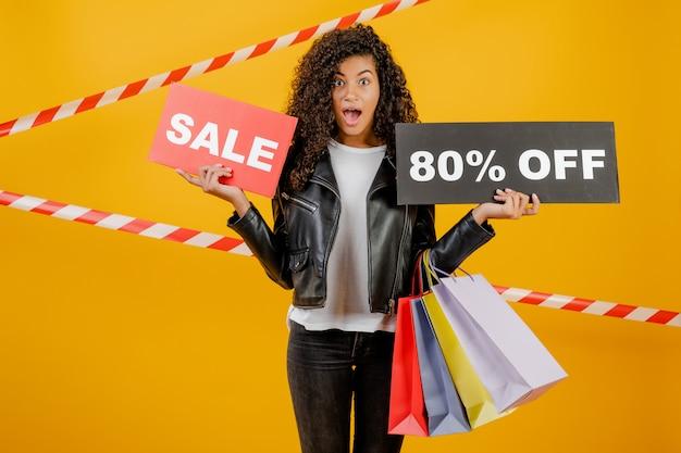 Modna młoda czarna dziewczyna ze znakiem 80% sprzedaży i kolorowe torby na zakupy odizolowane na żółto z taśmą sygnałową
