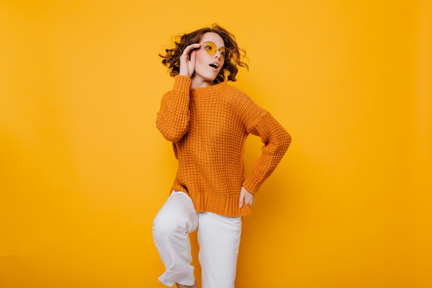 Modna młoda dama w sweterku i białych spodniach stoi na jednej nodze i odwraca wzrok z otwartymi ustami