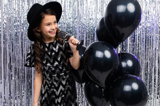 Modna młoda dziewczyna śpiewa w karaoke na imprezie z mikrofonem w dłoniach na błyszczących czarnych balonach z helem