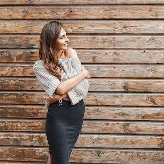 Modna młoda dziewczyna w szarym swetrze i czarnej spódnicy przy drewnianej ścianie