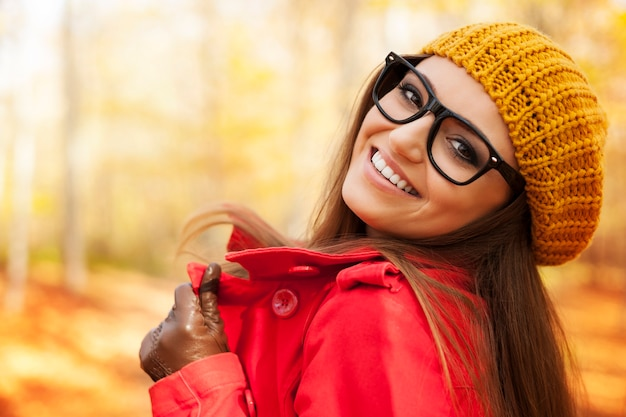 Modna młoda kobieta, ciesząc się w sezonie jesiennym
