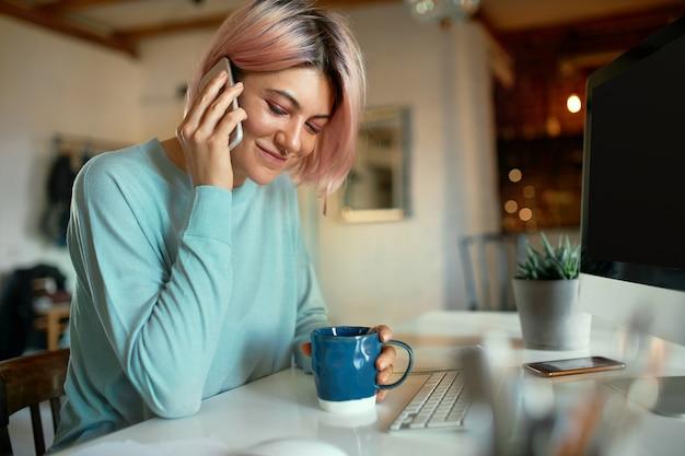 Modna młoda kobieta copywriter z różowymi włosami i kolczykiem na twarzy siedzi w swoim miejscu pracy przed komputerem, trzymając kubek, pijąc kawę i rozmawiając telefonicznie, uśmiechając się