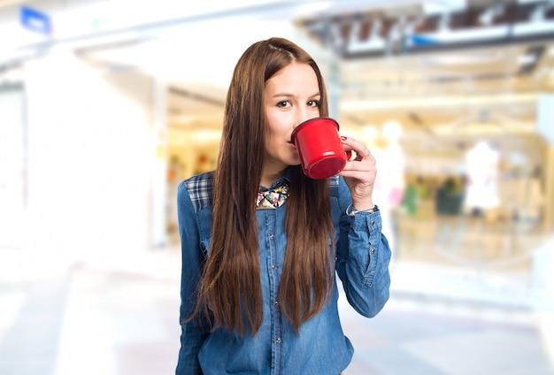 Modna młoda kobieta pije z czerwonym kubku