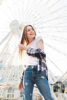 Modna młoda kobieta pozuje przed diabelskim młynem w parku rozrywki