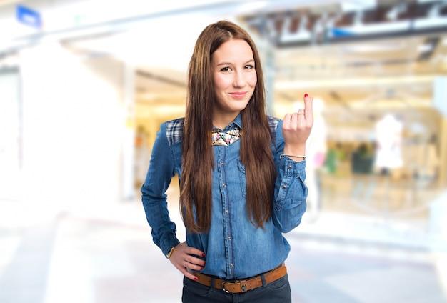 Modna młoda kobieta robi gest pieniędzy