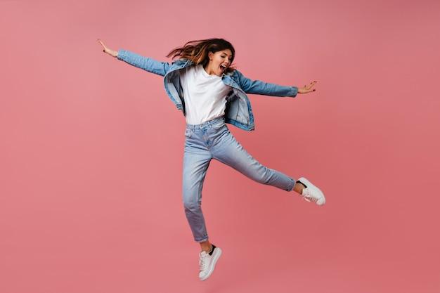 Modna młoda kobieta skacze na różowym tle. pełna długość beztroskiej modelki w jeansowym stroju.