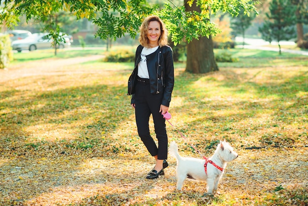 Modna młoda kobieta spaceru ze swoim małym west terrier highland white w parku. najlepsi przyjaciele.