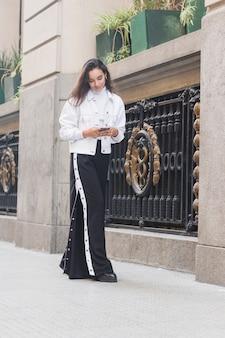 Modna młoda kobieta stoi na zewnątrz za pomocą telefonu komórkowego