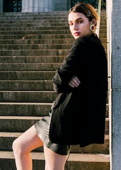 Modna młoda kobieta stoi przed schody z ręką skrzyżowaną