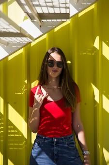 Modna młoda kobieta stojąca przy żółtej ścianie