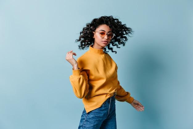 Modna młoda kobieta tańczy na niebieskiej ścianie