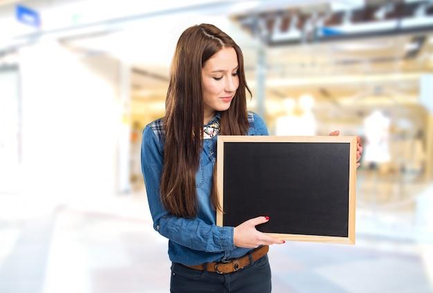 Modna młoda kobieta trzyma czarną deskę
