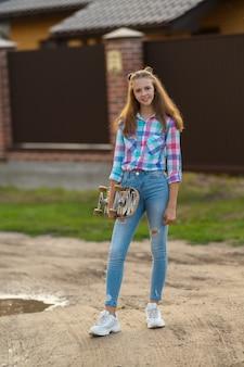 Modna młoda kobieta trzyma deskorolkę stojąc na zewnątrz, patrząc w kamerę z przyjaznym uśmiechem w wieczornym świetle