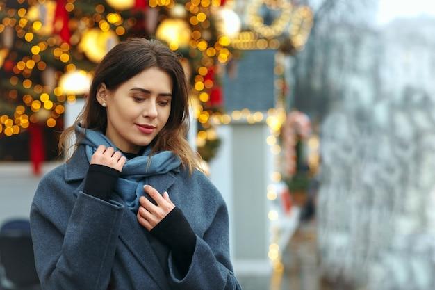 Modna młoda kobieta ubrana w modny płaszcz spaceru na ulicy w zimie. pusta przestrzeń