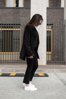 Modna młoda kobieta w czarnych ubraniach młodzieżowych dorywczo stoi w pobliżu zabytkowego budynku w mieście. zbliżenie. nowa wiosenna kolekcja stylowych ubrań dla kobiet.
