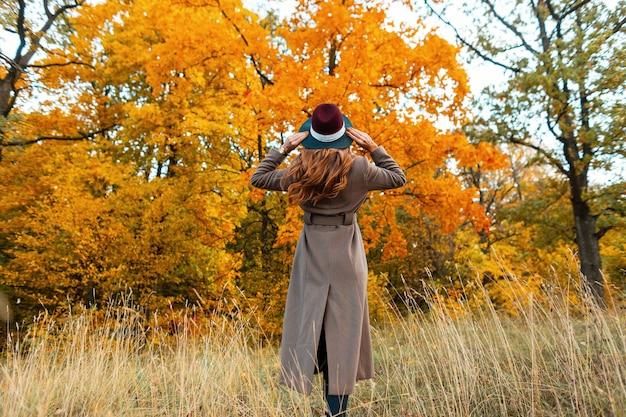 Modna młoda kobieta w eleganckim, długim płaszczu w stylowym kapeluszu stoi wśród suchej trawy i cieszy się jesienną scenerią w parku. dziewczyna spaceruje po lesie wśród złotych drzew. widok z tyłu