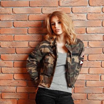Modna młoda kobieta w nowoczesnej kurtce wojskowej w pobliżu ściany z cegły