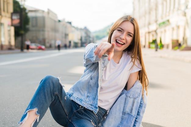 Modna młoda kobieta wskazuje przy kamery obsiadaniem na drodze