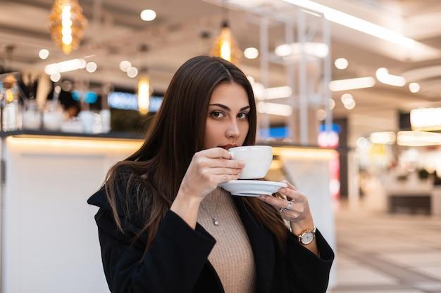 Modna młoda kobieta z długimi włosami w czarnym stylowym płaszczu siedzi i pije gorącą smaczną herbatę w kawiarni podczas przerwy. atrakcyjna europejska modelka cieszy się aromatycznym napojem w pomieszczeniu. dzień dobry.