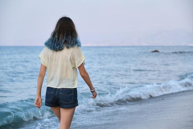 Modna młoda kobieta z farbowanymi długimi niebieskimi włosami spacerująca wzdłuż morza
