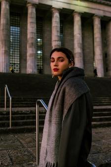 Modna młoda kobieta z jej wełnianym szalikiem wokoło jej szyi patrzeje kamerę