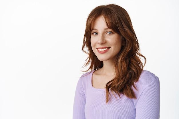 Modna młoda kobieta z piegami i białym uśmiechem, stojąca w fioletowej bluzce ze zrelaksowanym, szczęśliwym wyrazem twarzy