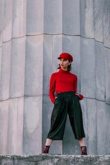 Modna młoda kobieta z rękami w kieszeni stoi przed dużym filarem