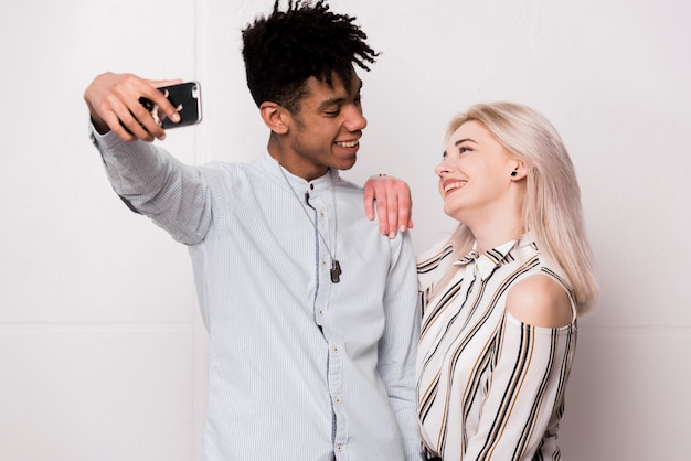 Modna młoda międzyrasowa uśmiechnięta para bierze selfie na smartphone