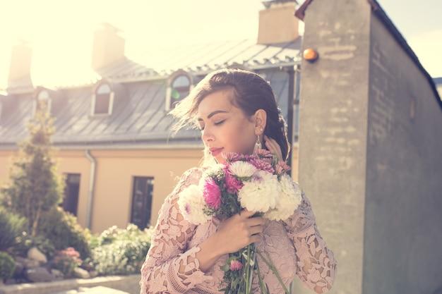 Modna młoda modelka w różowej sukience z kwiatami w ręce na tle miasta. efekt tonowania w stylu vintage