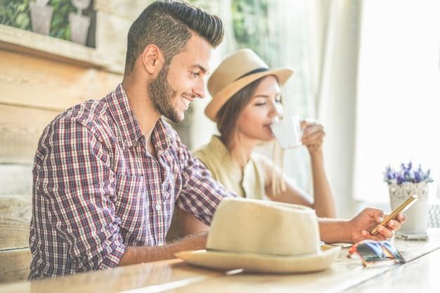 Modna młoda para picia kawy i korzystanie smartphone w kawiarni barze