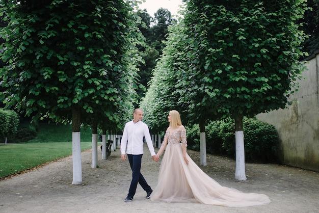 Modna młoda para spaceruje po mieście latem, młoda kobieta nosi luksusową sukienkę