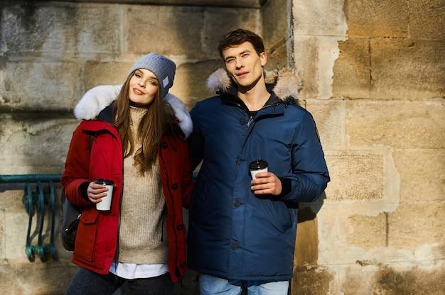 Modna młoda para spaceruje po mieście w czasie świąt bożego narodzenia
